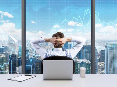 Vue arrière de l'homme d'affaires de détente avec les mains croisées derrière la tête, qui cherche à NYC. Bureau panoramique moderne ou lieu de travail de New York avec vue sur la ville. Tableaux financiers sont sur les fenêtres.