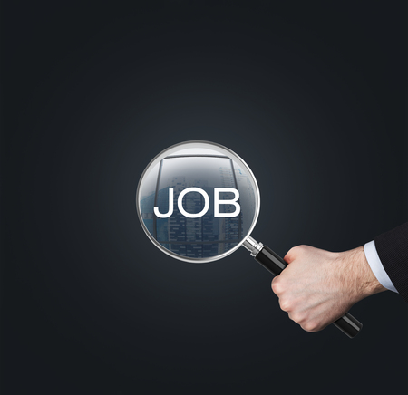 job qualifications: A hand holds a magnifying glass with the word JOB. The concept of the searching of the job. Dark background. Stock Photo