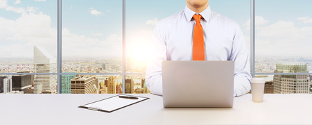 legal services: Young businessman is working with the laptop. Modern Panoramic office or work place with New York city view.