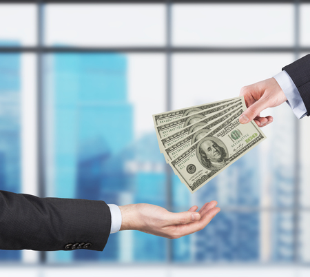 Two hands, money transferring process. Dollar bills. Business city view on the background form the panoramic windows of the modern office. Stock Photo