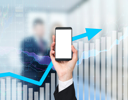 growing together: A hand holds a smartphone with copy space screen. Blank display. The arrow and graph are growing together over the background. A business couple in blur on the background.