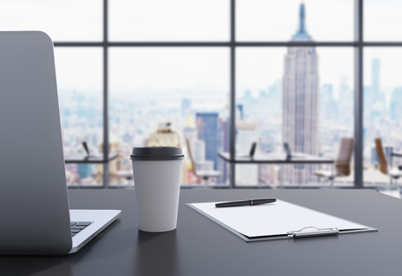 office window view: A workplace in a modern panoramic office in Manhattan, New York City. A laptop, notepad and a coffee cup are on the black table. 3D rendering. Stock Photo