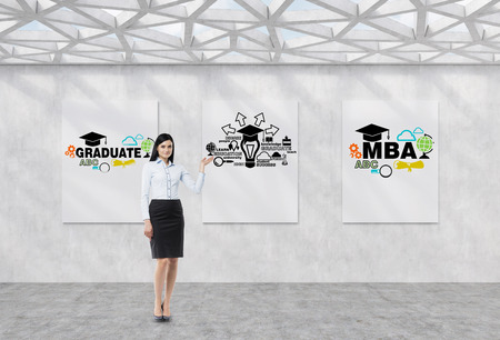 further education: Full length brunette girl in a formal clothes is pointing out the whiteboard with possible paths of further education. The concept of the MBA degree. Contemporary exhibition space. Stock Photo