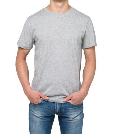 camisa: Un hombre en una camiseta y pantalones de mezclilla gris tiene las manos en los bolsillos. Aislado en blanco. Foto de archivo