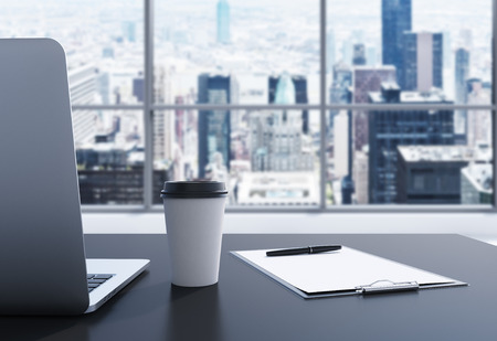 office window view: A workplace in a modern panoramic office in Manhattan, New York City. A laptop, notepad and a coffee cup are on the black table. 3D rendering. Toned image. Stock Photo
