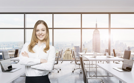 cross: Smiling beautiful business lady with cross hands is standing in a modern panoramic office in New York City. Manhattan sunset view. Toned image. Stock Photo