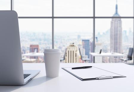 モダンなパノラマ事務所マンハッタン、ニューヨーク市での職場。ノート パソコン、メモ帳、コーヒー カップが白いテーブルです。3 D レンダリン