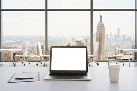 people laptop: Front view of the workplace in a modern panoramic office in New York. White tables and white chairs. A laptop with a white display, notepad and a coffee cup are on the table. 3D rendering.