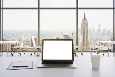 Vue de face du lieu de travail dans un bureau panoramique moderne à New York. tableaux blancs et des chaises blanches. Un ordinateur portable avec un écran blanc, bloc-notes et une tasse de café sont sur la table. le rendu 3D. Banque d'images
