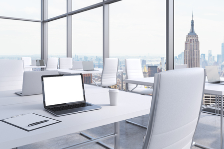 Workplaces in a modern corner panoramic office in Manhattan, New York City. White tables and white chairs. A laptop with a white screen, notepad and a coffee cup. 3D rendering. Stock Photo