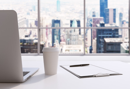 manhattan project: A workplace in a modern panoramic office in Manhattan, New York City. A laptop, notepad and a coffee cup are on the white table. 3D rendering. Toned image. Stock Photo