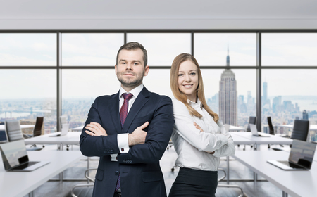 happy business team: Couple of young managers are standing in the modern panoramic office. New York, Manhattan panoramic view.