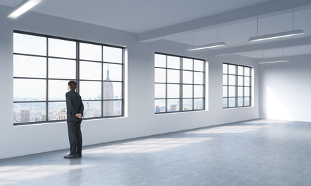 open business: A full length man in formal suit who is looking out the window, New York panoramic view. A modern loft style open space.