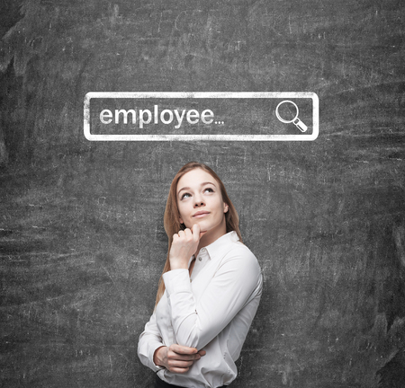 internet search: A beautiful recruiter by holding her chin is looking for new employees in the Internet. Internet concept of search available candidates. Black chalk board on the background. Stock Photo