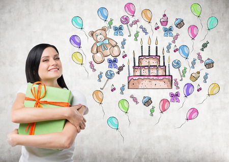 possessive: A brunette holds a green gift box. Colourful birthday celebration sketch is drawn on the concrete wall. Stock Photo