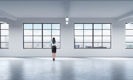 highkey: Rear view of a full length lady in formal clothes who is looking out the window in New York, modern loft style open space. Stock Photo