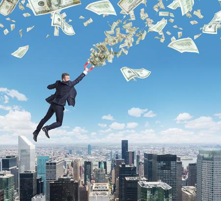 iman: Volar apuesto hombre de negocios confiados con el imán atrae a los billetes de dólar. la ciudad de Nueva York en el fondo. Foto de archivo