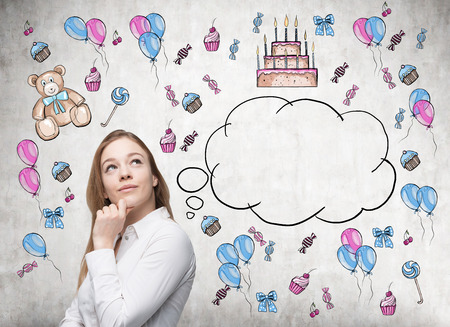 thinking woman: Astonishing lady is dreaming about her birthday. Birthday icons and an empty thoughts bubble are drawn on the concrete wall. Stock Photo