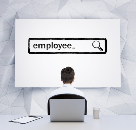 search bar: Rear view of a sitting person who looks at the whiteboard with the drawn searching bar with the word employee. A laptop, a writing pad and a cup of coffee are on the table. Stock Photo