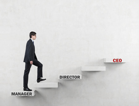 achiever: An ambitious man in a suit is going up the corporate ladder from the manager to CEO. Concrete background.