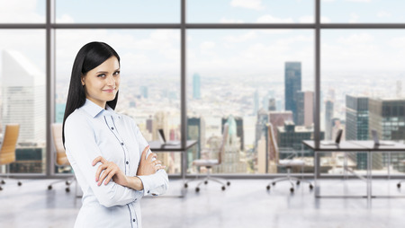 A side view of a beautiful smiling lady with crossed hands. The brunette woman is dressed in formal clothes. Modern workplaces in a fancy panoramic office in New York.