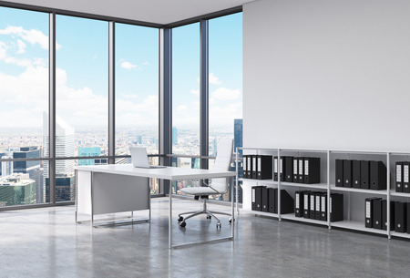 A CEO workplace in a modern corner panoramic office in New York city. A white desk with a laptop, white leather chair and a bookshelf with black document folders. 3D rendering.