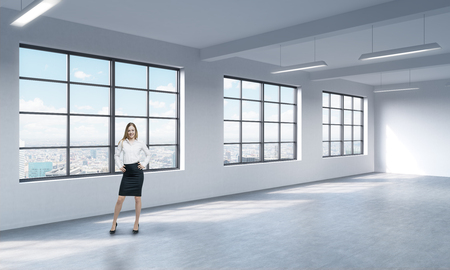 open space: A full length woman in formal clothes who is looking out the window, New York panoramic view. A modern loft style open space.