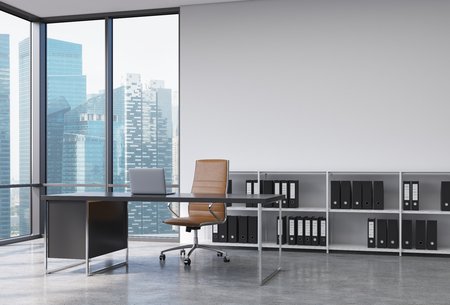 design office: A CEO workplace in a modern corner panoramic office with Singapore city view. A black desk with a laptop, brown leather chair and a bookshelf with black document folders. 3D rendering. Stock Photo
