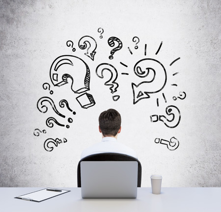 question marks: Rear view of a sitting person at the working desk who is looking for the best solution of the problem. Question marks are drawn on the concrete wall. Stock Photo