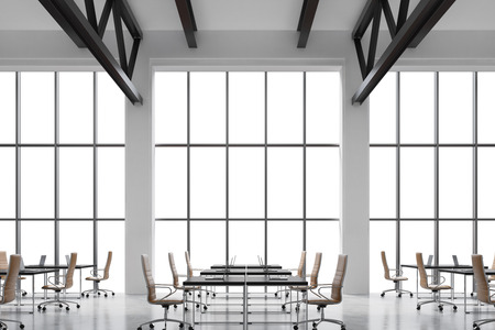 company premises: Modern workplaces in a modern bright clean interior of a loft style office. Huge windows with copy space and white walls. Black desks equipped with laptops, brown leather chairs. 3D rendering.