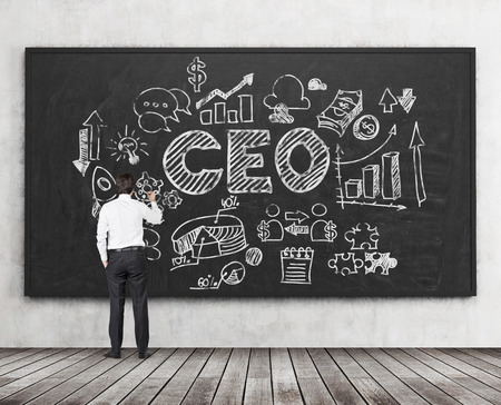 executor: A full length rear view of an ambitious young professional who is drawing the flowchart on the blackboard, in a central part of the flowchart is acronym CEO. Wooden floor and concrete wall in a room.