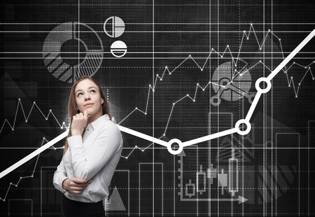 financial performance: Beautiful young professional with the hand which holds her chin is thinking about future opportunities of the project. Financial analytic charts are drawn on the background.