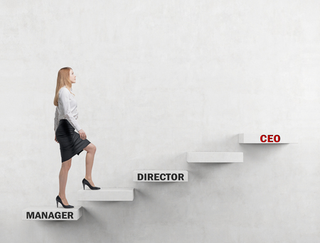 corporate ladder: A young business lady is going up the corporate ladder from the manager to CEO. Concrete background. Stock Photo