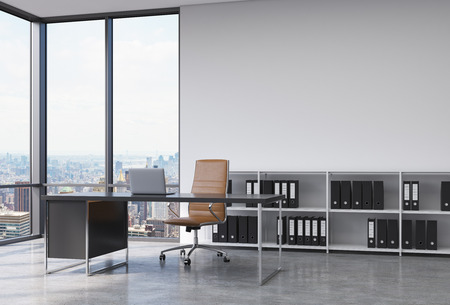 panoramic windows: A CEO workplace in a modern corner panoramic office with New York city view. A black desk with a laptop, brown leather chair and a bookshelf with black document folders. 3D rendering. Stock Photo