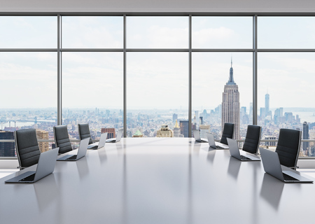 A conference room equipped by modern laptops in a modern panoramic office in New York. Black leather chairs and a white table. 3D rendering. Stock Photo