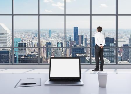 persona escribiendo: Una persona vestida con ropa formal está de pie en la oficina moderna panorámica y mirando a Nueva York. Un ordenador portátil con pantalla en blanco, un panel de escritura y una taza de café sobre la mesa blanca. Foto de archivo