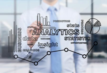 Een zakenman of een medewerker is het tekenen van een analytics optimalisatie grafiek op het glazen scherm in een modern panoramisch kantoor in New York. Stockfoto