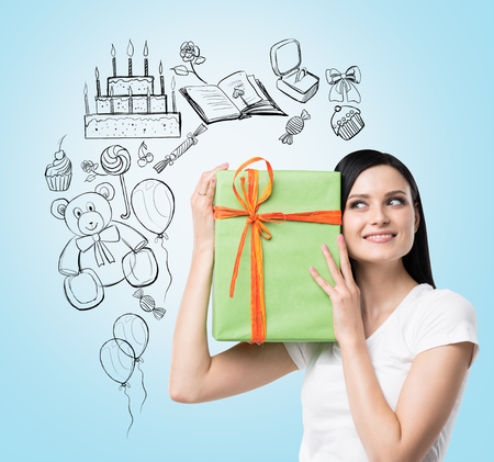 and guessing: A brunette holds a green gift box. Birthday celebration sketch is drawn on the light blue background.