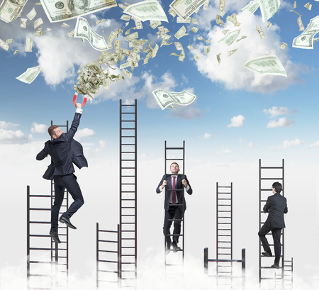 corporate greed: Confident handsome businessman on the ladder attracts dollar notes using a magnet. Sky with clouds on the background. Stock Photo