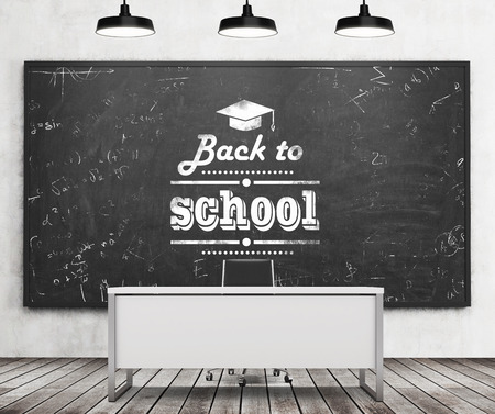 Teachers desk in a modern university or school. A huge black chalkboard on the wall with written down phrase - Back to school. Three black ceiling lights and wooden floor. 3D rendering. Stock Photo
