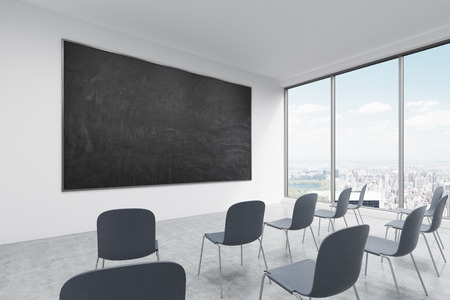 angled view: A classroom or presentation room in a modern university of fancy office. Black chairs, panoramic windows with New York view and a black chalkboard on the wall. 3D rendering.