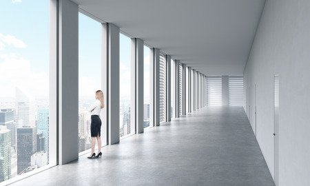 open windows: A woman in formal clothes is looking out the window. Empty modern bright clean interior of an open space office. Huge panoramic windows with New York view.
