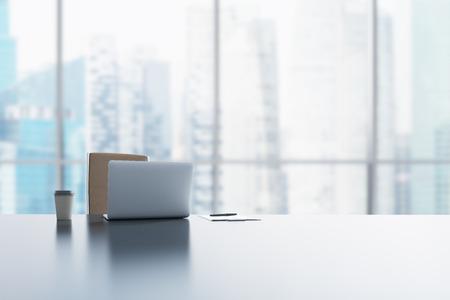 Een werkplek in een modern panoramisch kantoor in Singapore. Een laptop, notitieblok en een kopje koffie op de witte tafel. 3D-rendering. Stockfoto
