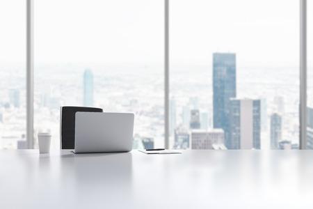 Um local de trabalho em um escritório panorâmico moderno em Manhattan, New York City. Um laptop, bloco de notas e um copo de café estão sobre a mesa branca. Renderização 3D. Banco de Imagens