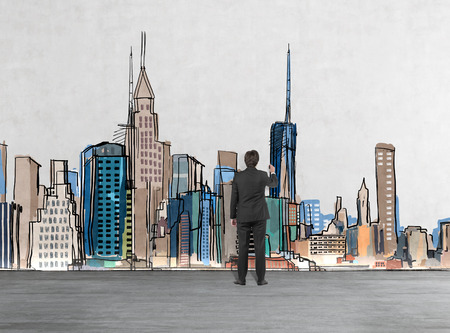 estate planning: Rear view of a businessman who is drawing New York picture on the wall. A concept of financial consultancy. Stock Photo