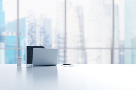 Een werkplek in een modern panoramisch kantoor in Singapore. Een laptop, notitieblok en een kopje koffie op de witte tafel. 3D-rendering. Stockfoto - 46534974