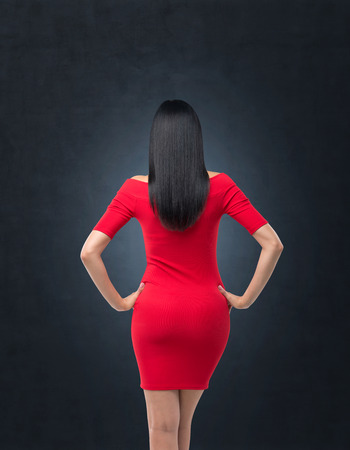 Rear view of gorgeous brunette in red dress posing on black background.