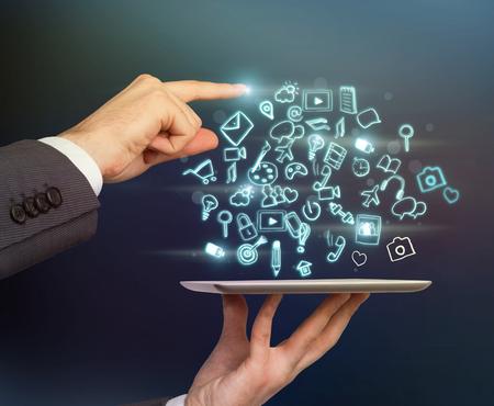 dedo: Primer plano de las manos del hombre de negocios y un dedo que est� se�alando el icono espec�fico en la proyecci�n de la tableta. iconos de redes sociales est�n volando en el aire. la imagen en tonos. Foto de archivo