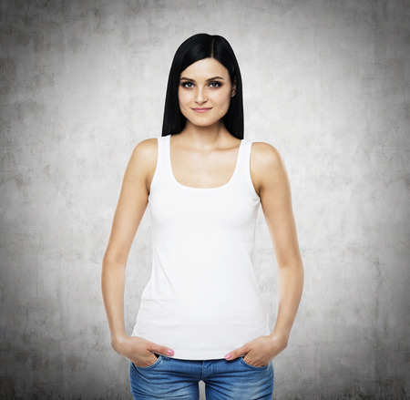 tanktop: A brunette woman in a white tank top and denims. Hands are in the pockets. Concrete background.