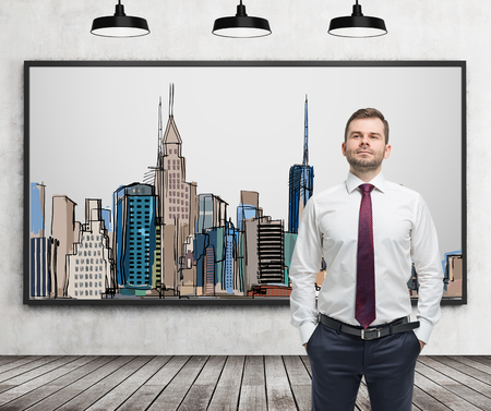 shirtsleeves: A handsome man in formal clothes stands in front of the picture of New York City on the wall. Wooden floor, concrete wall and three black ceiling lights.